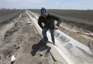 Gine Celli climbing out of an irrigation canal that is covered in dried salt on a farm near Stockton, Calif. New studies warn about the depletion rates of aquifers in food-producing regions that support up to two billion people.Rich Pedroncelli/Associated Press